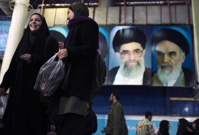FILE PHOTO: Iranian women walk in front of the pictures of Ayatollah Ruhollah Khomeini, the founder of the Islamic Republic (R) and Iran's Supreme Leader Ayatollah Ali Khamenei. Reuters