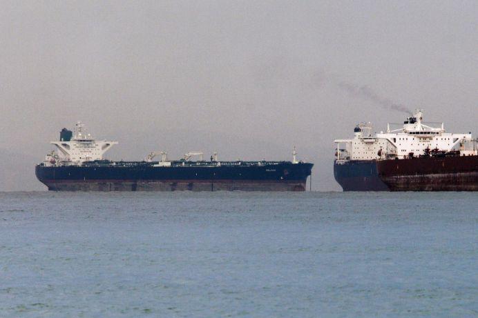 "FILE PHOTO: Vessels sail past Malta-flagged Iranian crude oil supertanker ""Delvar"" (L) anchoring off Singapore. REUTERS/Tim Chong"