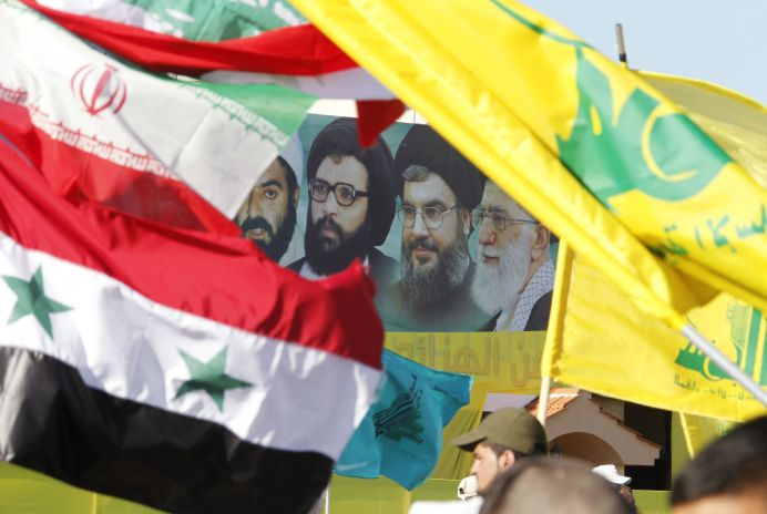 FILE PHOTO: A poster of (R-L) Iran's supreme leader Ayatollah Ali Khamenei, Hezbollah Secretary-General Sayyed Hassan Nasrallah, former Hezbollah Secretary-General Sayyed Abbas al-Musawi and Lebanese resistance leader and cleric Sheikh Ragheb Harb, is seen in between Iranian, Syrian, Lebanese and Hezbollah flags. REUTERS/Ali Hashisho