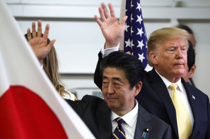 U.S. President Donald Trump and Japan's Prime Minister Shinzo Abe wave after delivering a speech to Japanese and U.S. troops as they aboard Japan Maritime Self-Defense Force's (JMSDF) helicopter carrier DDH-184 Kaga at JMSDF Yokosuka base in Yokosuka, south of Tokyo, Japan, May 28, 2019. REUTERS