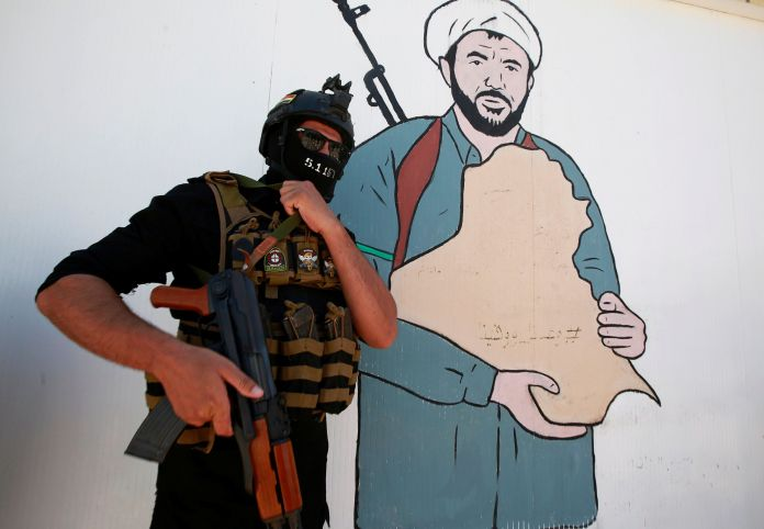 FILE PHOTO: A member of Iraqi Popular Mobilization Forces (PMF) poses for a picture near a drawing of PMF member at their headquarters in the holy city of Najaf, Iraq July 2, 2019. REUTERS/Alaa Al-Marjani
