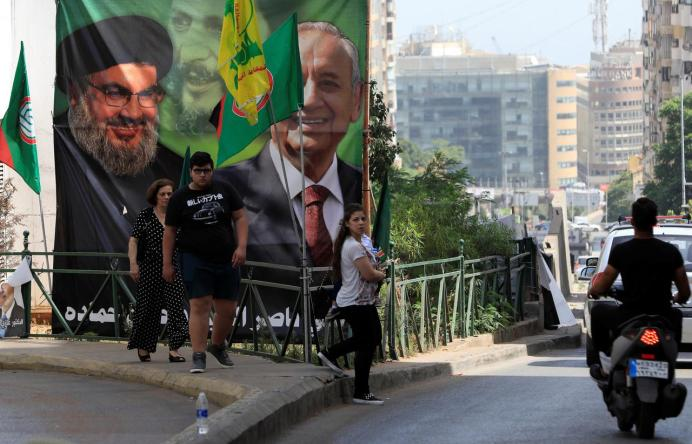 FILE PHOTO: People walk past a campaign banner showing Lebanese Parliament Speaker and candidate for parliamentary election Nabih Berri and Hezbollah leader Sayyed Hassan Nasrallah in Beirut, Lebanon May 4, 2018. REUTERS/Jamal Saidi
