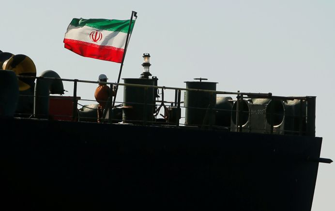FILE PHOTO: A crew member raises the Iranian flag at Iranian oil tanker Adrian Darya 1, before being named as Grace 1.REUTERS/Jon Nazca