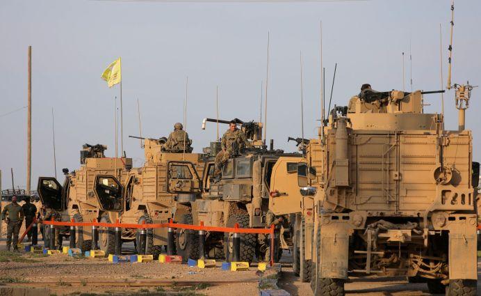 FILE PHOTO: American soldiers stand near military trucks, at al-Omar oil field in Deir Al Zor, Syria March 23, 2019. REUTERS/Rodi Said.
