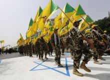 FILE PHOTO: Iraqi Shi'ite Muslim men from the Iranian-backed group Kataib Hezbollah wave the party's flags as they walk along a street painted in the colours of the Israeli flag during a parade marking the annual Quds Day, or Jerusalem Day, on the last Friday of the Muslim holy month of Ramadan, in Baghdad July 25, 2014. REUTERS./