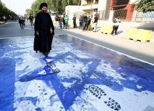 A supporter of Qais al-Khazali, leader of the Asaib Ahl al-Haq Iran-backed militia group, walks over an Israeli flag during a demonstration against U.S. sanctions targeting al-Khazali, in Baghdad, Iraq, December 14, 2019. REUTERS/Alaa al-Marjani