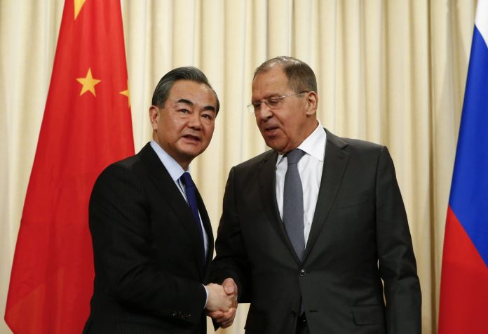 FILE PHOTO: Russia's Foreign Minister Sergei Lavrov (R) shakes hands with China's top diplomat State Councillor Wang Yi during a news conference in Moscow. REUTERS/Sergei Karpukhin