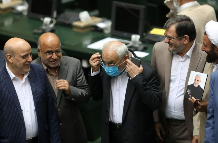 An Iranian lawmaker wears a protective face mask, as he attends the opening ceremony of Iran's 11th parliament, as the spread of the coronavirus disease (COVID-19) continues, in Tehran, Iran, May 27, 2020.