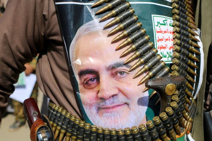"""FILE PHOTO: A supporter of the Houthis has a poster attached to his waist of Iranian Major-General Qassem Soleimani, head of the elite Quds Force, who was killed in an air strike at Baghdad airport. The writing on the poster reads: """"God is the Greatest, Death to America, Death to Israel, Curse on the Jews, Victory toIslam."""" REUTERS/Naif Rahma"""