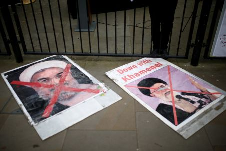 FILE PHOTO: Placards depicting Iranian President Hassan Rouhani and the Supreme Leader lie on the ground during a vigil for the victims of a Ukrainian passenger jet which shot down by IRGC's missiles in Iran. REUTERS/Henry Nicholls
