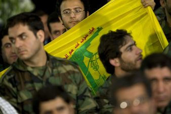A member of Iran's basij militia holds a Lebanese Hezbollah flag during the anniversary ceremony of Iran's Islamic Revolution at the Khomeini shrine in the Behesht Zahra cemetery, south of Tehran. REUTERS./