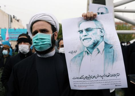 In a state sponsored event, a participant holds a picture of Mohsen Fakhrizadeh, during a demonstration against his killing in Tehran, Iran, November 28, 2020.