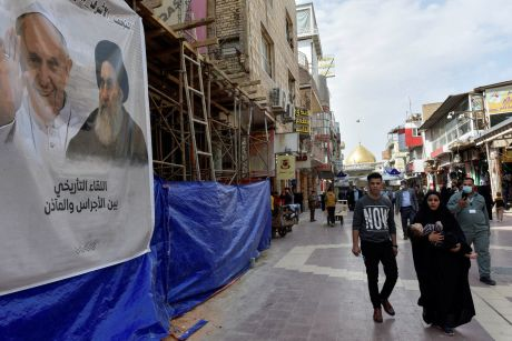 People walk past a poster of Pope Francis and Iraq's top Shi'ite cleric, Ayatollah Ali al-Sistani, ahead of the Pope's planned visit to Iraq, in Najaf, Iraq, March 4, 2021. REUTERS/ Alaa Al-Marjani
