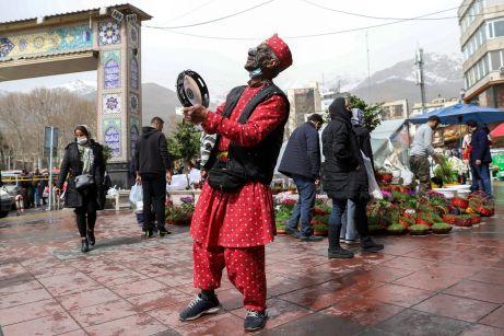 "An Iranian style Santa Claus called "" Haji Firuz"" dances at the Tajrish Bazaar, ahead of Nowruz, the Iranian New Year, amid the coronavirus disease (COVID-19) pandemic, in Tehran, Iran March 17, 2021. REUTERS./"