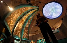 A V&A employee looks up at the Dome Projection and triangular paintings recreating tiled interiors of mosque domes in Isfahan which are on display at Epic Iran, an exhibition soon to open at the V&A in London, Britain, May 25, 2021. Picture taken May 25, 2021. REUTERS/Peter Nicholls