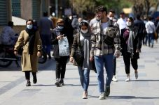 Iranian people wear protective face masks, as they walk amid the spread of the coronavirus disease (COVID-19), in Tehran, Iran. REUTERS/FILE PHOTO./