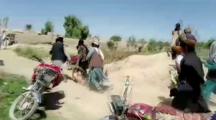 Men said to be Taliban fighters drag the body of a man on the ground at a location said to be Farah, Afghanistan, in this still image taken from an undated recent video obtained by Reuters August 11, 2021. Video obtained by REUTERS./