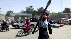 A Taliban fighter runs towards crowd outside Kabul airport, Kabul, Afghanistan August 16, 2021, in this still image taken from a video. REUTERS./