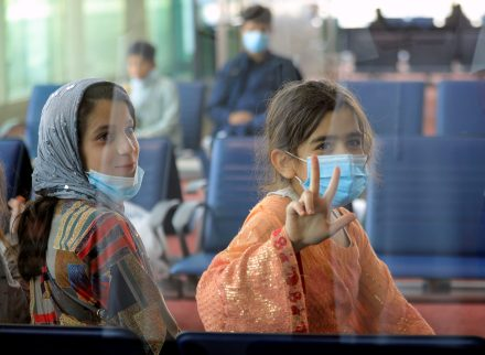 Evacuees from Afghanistan are seen through a glass window as they sit in a hall upon their arrival at Al Maktoum International Airport (DWC) in Dubai, United Arab Emirates, August 19, 2021. REUTERS/Rula Rouhana