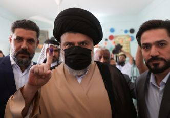 Iraqi Shi'ite cleric Muqtada al-Sadr shows his inked finger after voting at a polling station in Najaf, as Iraqis go to the polls to vote in the parliamentary election, in Iraq, October 10, 2021. REUTERS/