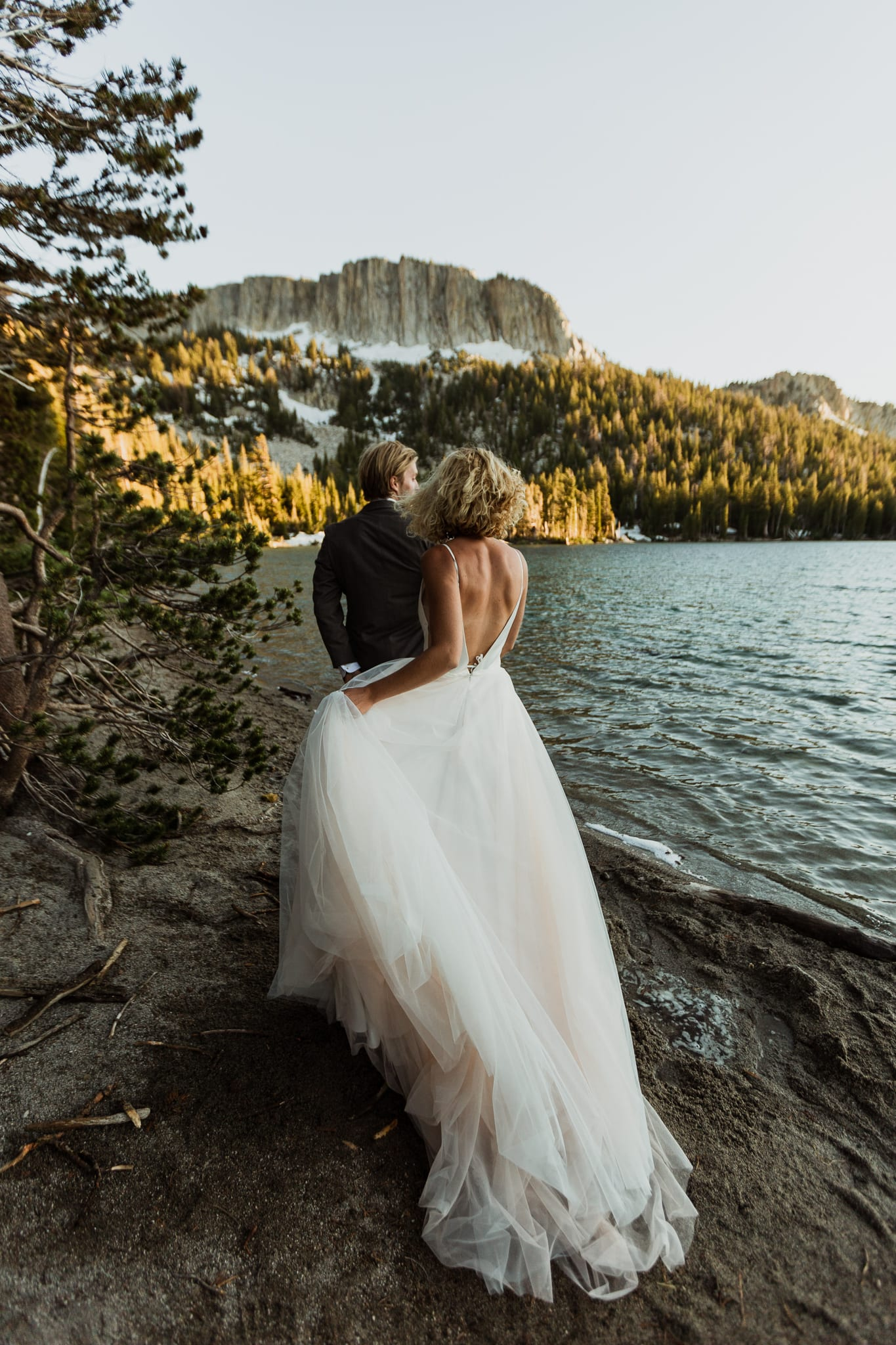 A bride and groom walk closely to the edge of McLeod in Mammoth Lakes. They are facing the tall Mammoth Crest ridge with the sun setting on them to their right.