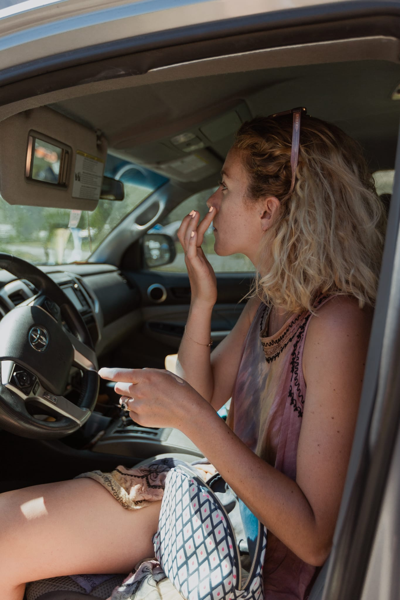 Haylee uses the driver's sun visor mirror to put her elopement makeup on!