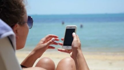 Millennial on the beach with a device