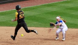 Sami Fagan (51) runs in front of shortstop Chaley Brickey, causing her to miss the ground ball.