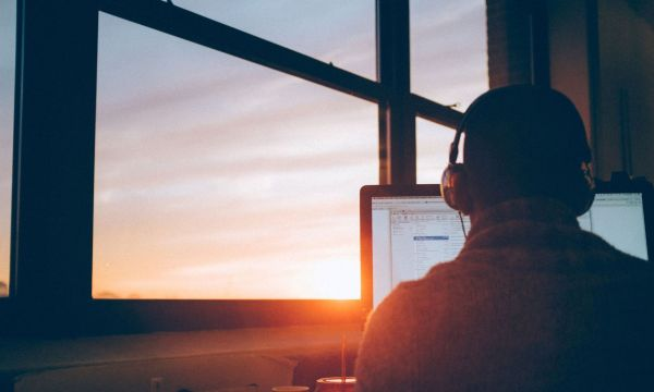 the back of a person on their computer with headphones on, next to a window at sunset