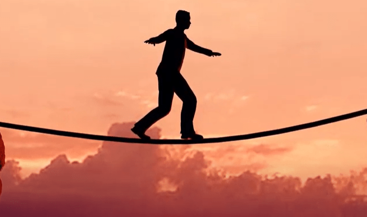 silhouette of person walking tightrope
