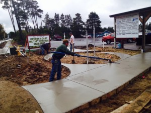 A crew from Center Brothers Construction works on finishing concrete in the OCMHM Remembrance Garden this week.  (photo by Wayne Sharpe)