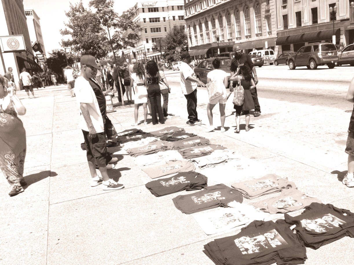 Street vendors sell commemorative shirts.