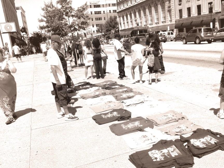 Street vendors sell commemorative shirts.