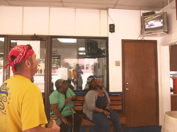 Louisville residents watch live coverage of Ali's funeral procession on a television inside a car wash.