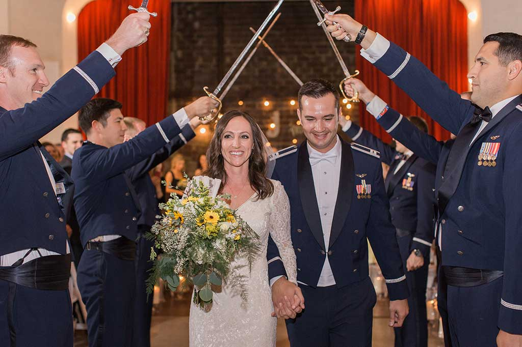 Military wedding with Bride and Groom walking through the arch of swords