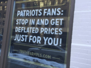 Sign reading Patriots Fans: Stop in and get deflated prices just for you! truthbarmpls.com