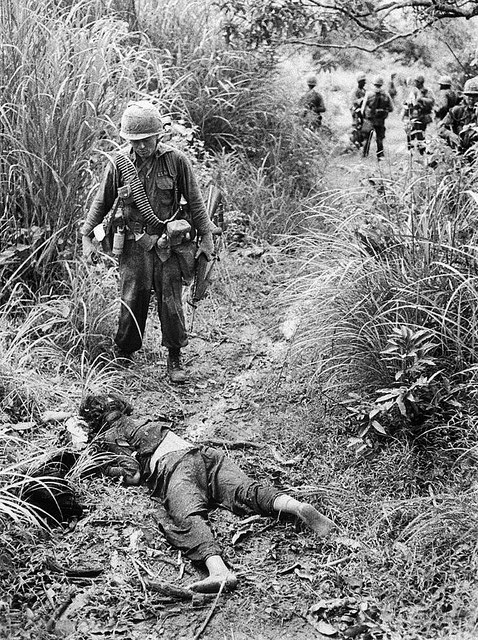 A black-and-white photo. As his men wait for him in the background, a patrol leader from a unit of the U.S. 1st Cavalry Division sorrowfully looks down at a dead Vietnamese woman.