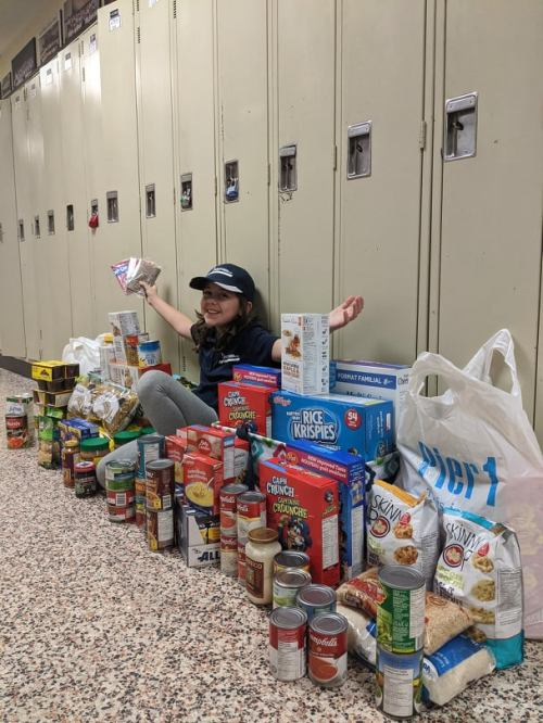 young girl sitting among non-perishable food items for food bank donation
