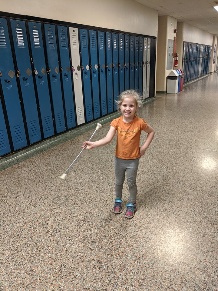 young girl standing in a school hallway practicing twirling a baton while smiling
