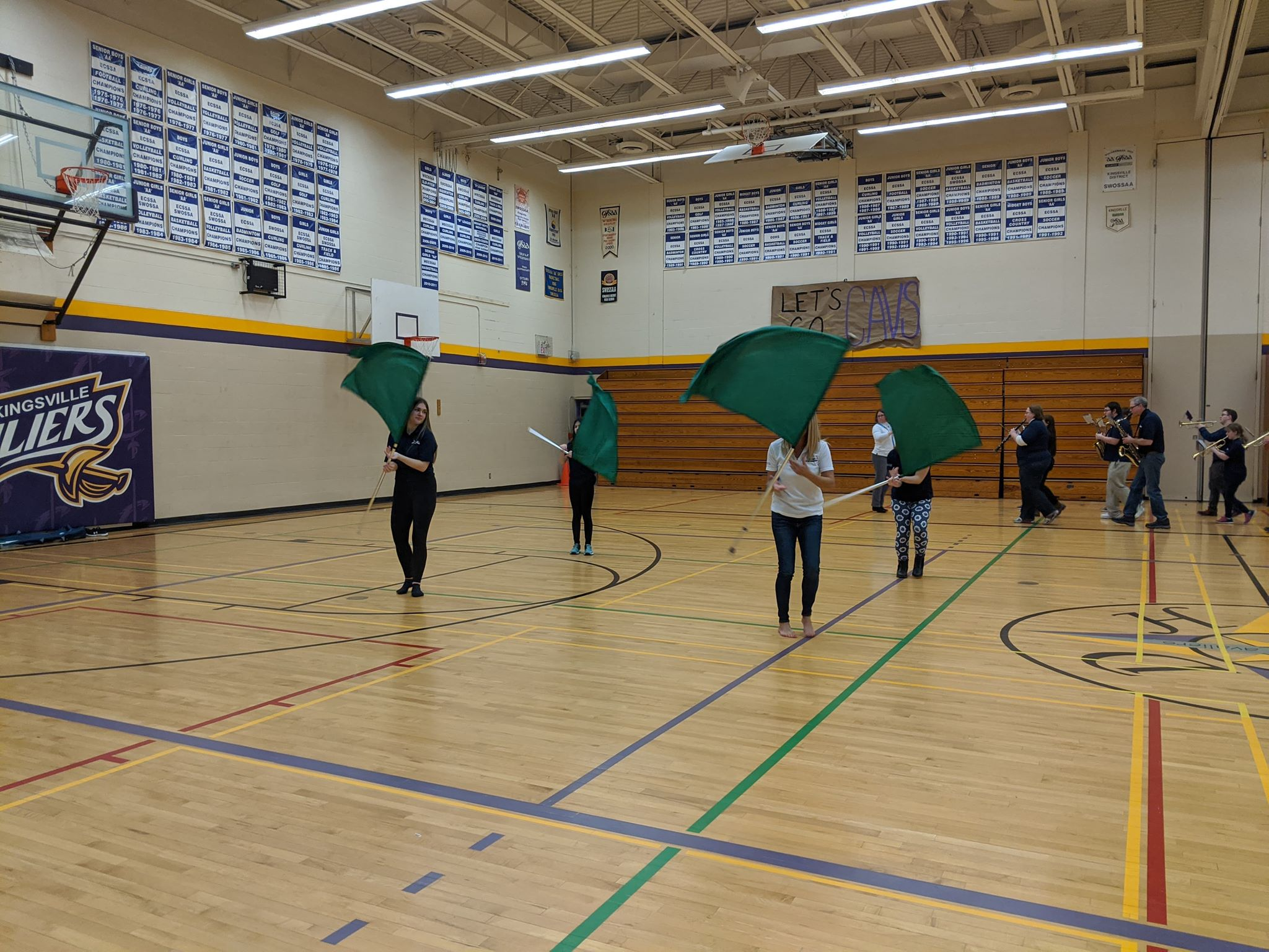members of the colour guard practicing in a gymnasium with green flags
