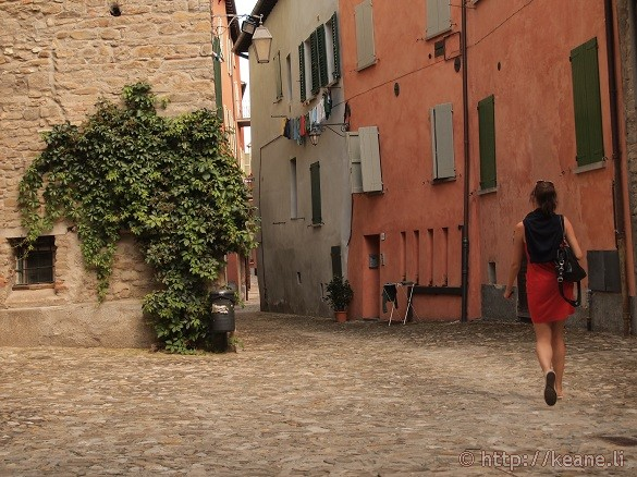 Hidden piazza in Brisighella and woman in red dress