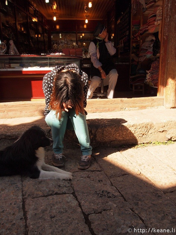 Girl with head in hands and dog in Lijiang Old Town