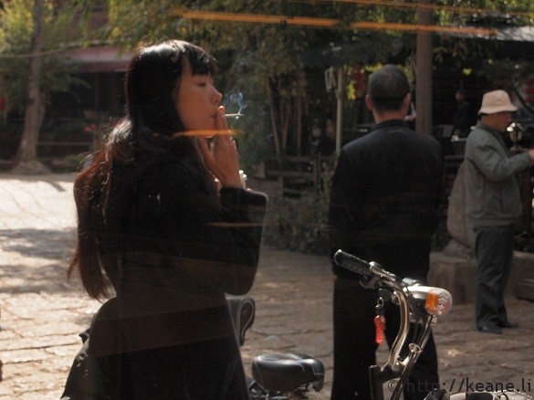 Hip Chinese woman smoking outside bakery window in Shu He Ancient City