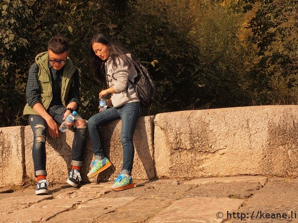 Chinese couple with colorful shoes along Qinglong Bridge in Shu He Ancient City