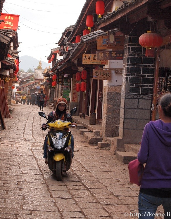 Fashionable Chinese girl rides scooter down street in Shu He Ancient City