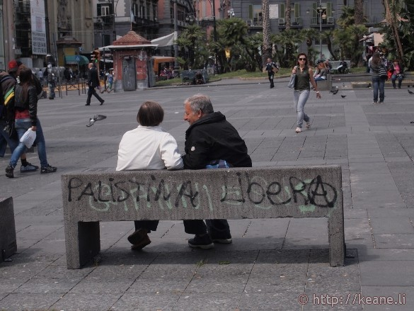 Old couple on a bench with graffiti in Piazza Dante in Naples