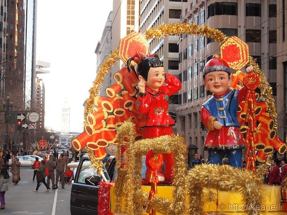 Chinese couple float for Chinese New Year parade with Ferry Building in background