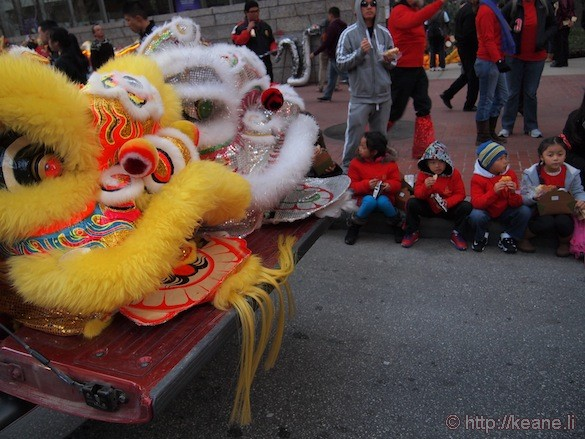 Chinese lion heads and kids eating before the Chinese New Year parade