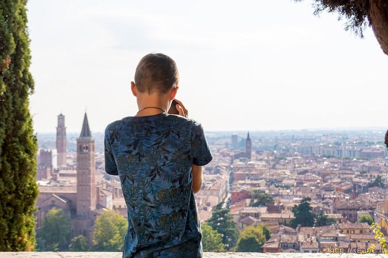 Boy Looking Through Binoculars at Castel San Pietro over Verona