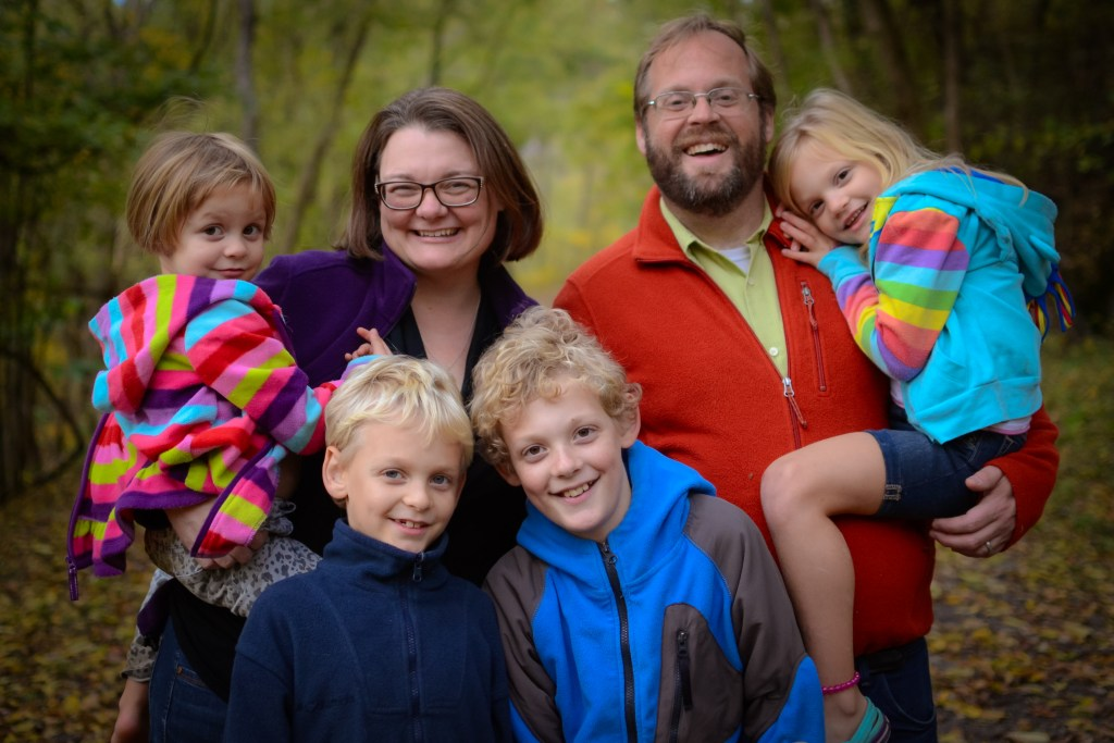 Photo of a family of 6 on a wooded trail